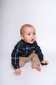 Grappige kleine jongen met een telefoon op een witte achtergrond