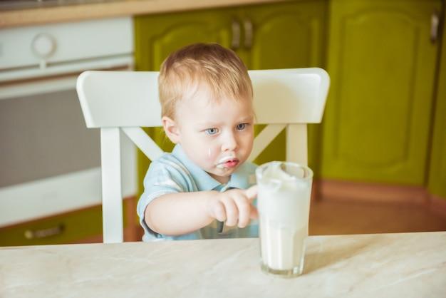 Grappige kleine jongen met snor van melk