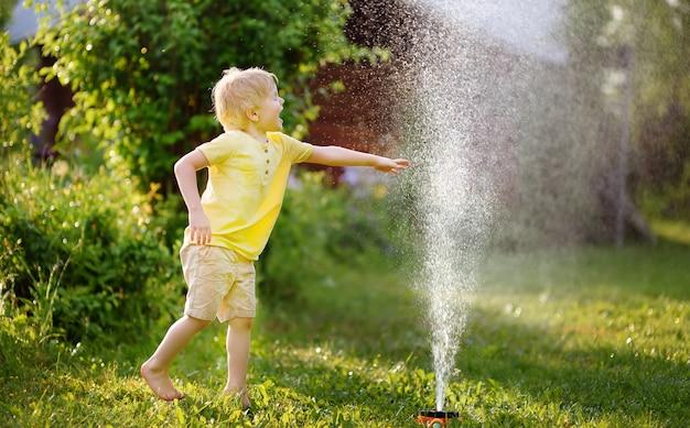 Grappige kleine jongen spelen met tuin sprinkler in zonnige achtertuin