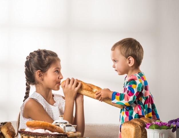 Grappige kleine kinderen eten vers brood en broodjes