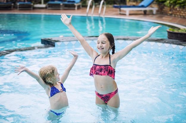 Grappige kleine kindermeisjes glimlachen en zwemmen in het buitenzwembad, mooi en gelukkig