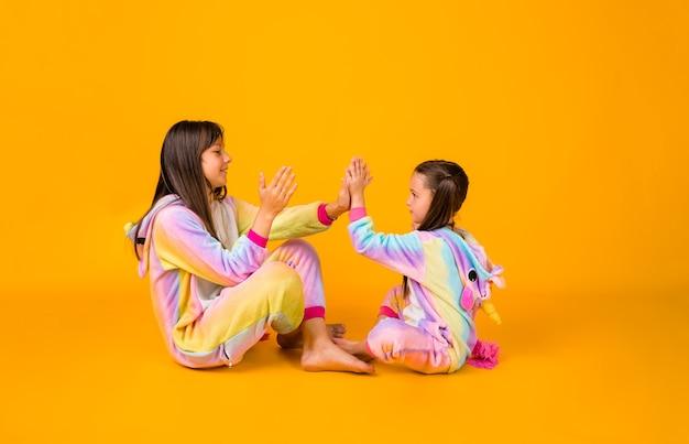Grappige kleine meisjes in pluche pyjama's spelen op een gele achtergrond met een kopie van de ruimte