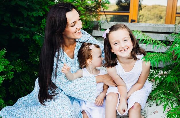 Grappige kleine meisjes zitten in de knuffels van de moeder op voetstappen omgeven met groen