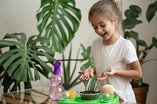 Grappige kleine meisjestuinman met planten in de kamer thuis, water geven en zorgen voor kamerplanten, bloemen transplanteren.