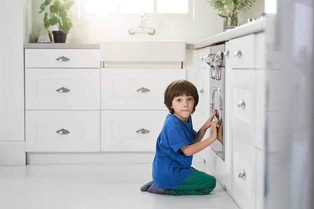 Grappige kleine spaanse jongen die verbaasd naar de camera kijkt terwijl hij kijkt naar het bakken van cake in de oven, gehurkt in de keuken. kinderen, kookconcept. zijaanzicht