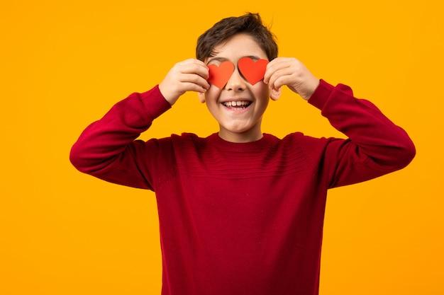 Grappige knappe blanke jongen met twee papieren kaarten in de vorm van harten voor valentijnsdag onn oranje