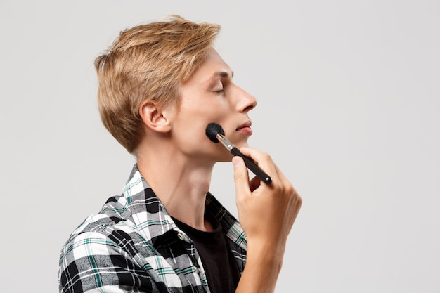 Grappige knappe blonde jonge man met casual geruite overhemd met make-up borstel over grijze muur