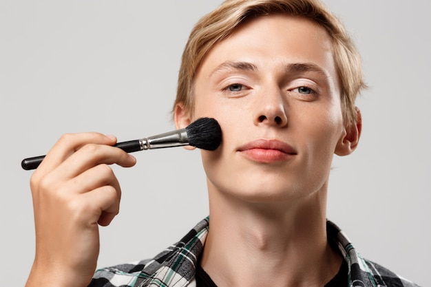 Grappige knappe blonde jonge man met casual geruite overhemd met make-up borstel