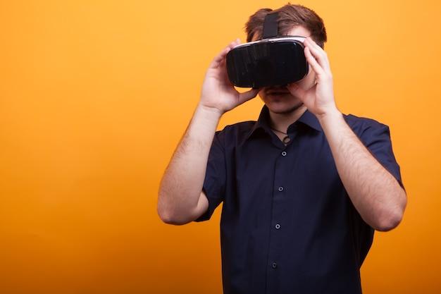 Grappige knappe jongeman in blauw shirt en zijn vr-headset op gele achtergrond. nieuwe gadget