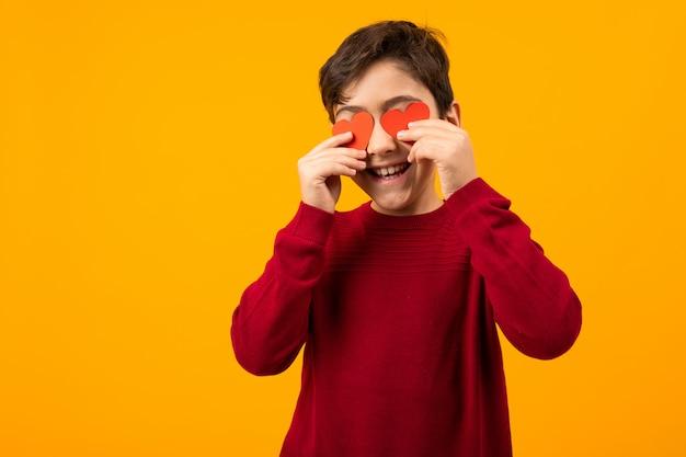 Grappige knappe kaukasische jongen met papieren kaarten in de vorm van harten voor valentijnsdag onn oranje