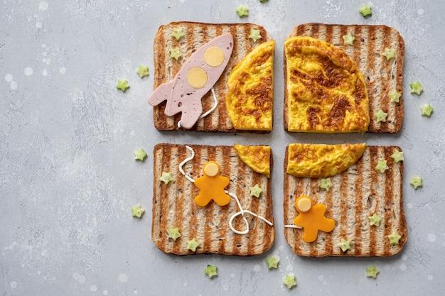 Grappige kosmos sandwiches met raket en astronauten op de omeletmaan