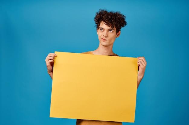 Grappige krullende jongens met een gele scherpe advertentie kopie ruimte blauwe achtergrond