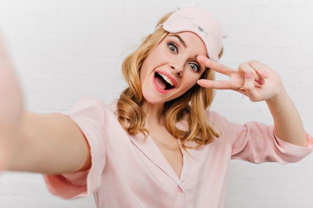 Grappige krullende vrouw in roze slaapmasker selfie maken. indoor zelfportret van glamoureuze blonde meisje in zijden nachtkostuum geïsoleerd op een witte muur.