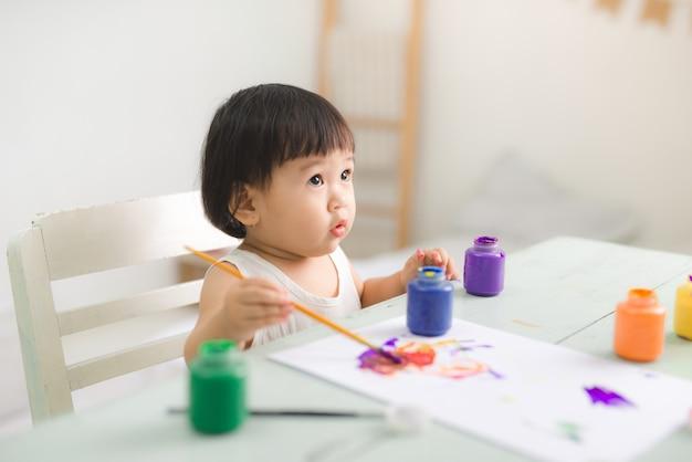 Grappige lachende aziatische babymeisje tekenen met kleurrijke potloden thuis