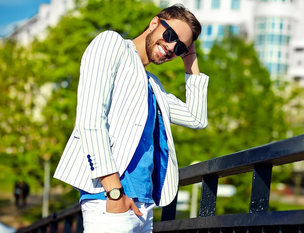 Grappige lachende hipster knappe man in stijlvolle zomer wit pak poseren in straat in zonnebril