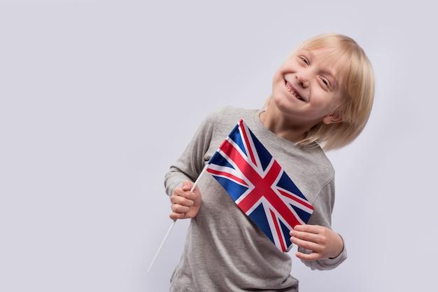Grappige lachende jongen met engelse vlag op witte achtergrond. reis met kinderen naar groot-brittannië.