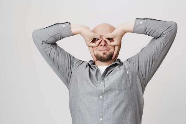 Grappige lachende man toont superheld masker met vingers