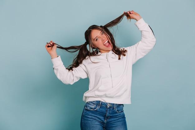 Grappige lachende vrouw die met haar haar speelt dat gezichten maakt en over geïsoleerde muur danst