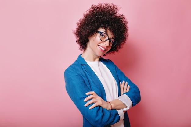 Grappige lachende vrouw met ringetjes draagt een bril en blauw jasje vormt op roze