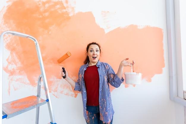 Grappige lachende vrouw schilderij binnenmuur van huis met verfroller. herinrichting, renovatie