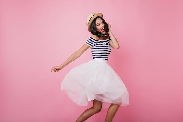Grappige latijns-vrouw in strohoed geluk uitdrukken en dansen. emotioneel vrouwelijk model in het witte rok stellen