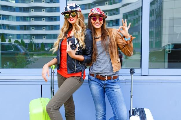 Grappige levensstijl portret van vrij beste vrienden meisjes plezier voor hun reis, poseren met bagage in de buurt van luchthaven, lichte sportieve casual kleding en zonnebril dragen, klaar voor nieuwe emoties