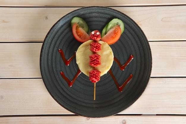 Grappige maaltijd voor kinderen. aardappelpuree met gebakken worst aan het spit met tomaat en komkommer
