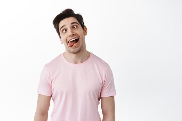 Grappige man die grimassen en tong toont, speels leuke gezichten maakt, voor de gek houdt, tegen een witte muur staat