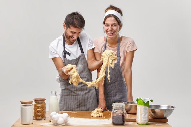 Grappige man draagt een schort, probeert gebak te koken, rekt plakkerig deeg uit, heeft kookproblemen, vrolijke huisvrouw staat in de buurt, omringd met bakproducten op tafel, probeer koekjesrecept, poseer in de keuken