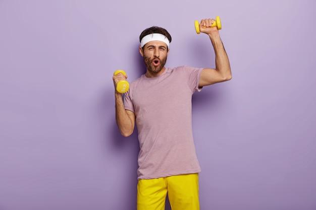 Grappige man heeft plezier, oefeningen met halters, gekleed in actieve kleding, gemotiveerd voor een gezonde levensstijl, heeft regelmatig training in de ochtend