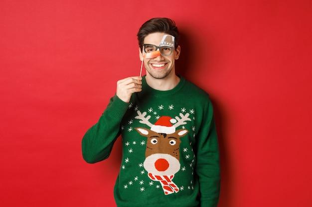 Grappige man in kersttrui en feestmasker, wintervakantie vieren, gelukkig glimlachen, over rode achtergrond staan