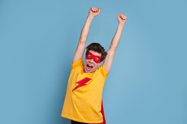 Grappige man in superheld masker schreeuwen en armen opheffen tijdens het vieren van de overwinning tegen blauwe achtergrond