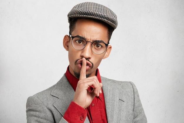 Grappige man met donkere gezonde huid draagt een ronde bril, houdt de vinger op de lippen, maakt stilte-teken