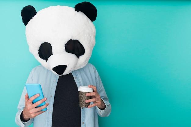 Grappige man met een berenmasker met telefoon terwijl hij koffie drinkt over een blauwe muur