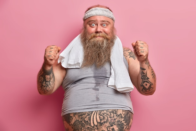 Grappige man met overgewicht die bezweet is na intensieve cardio, gebalde vuisten opheft, gekleed in sportkleding, ochtendoefeningen doet om af te vallen en alles in het werk stelt om fit en gezond te zijn. sport en zwaarlijvigheid