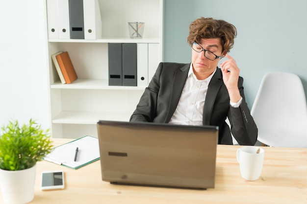 Grappige man moe na het werken op de computer op kantoor
