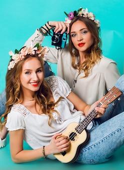 Grappige maniermeisjes die op blauwe muurachtergrond stellen in de uitrusting van de de zomerstijl met bloemenkroon die jeans en bohotaspak dragen. .