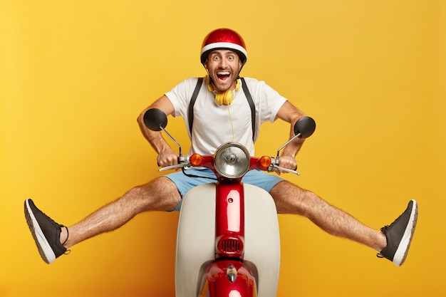 Grappige mannelijke scooter bestuurder vormt op scooter, houdt benen zijwaarts, draagt beschermende helm, wit t-shirt en blauwe korte broek, draagt rugzak op schouders geïsoleerd op gele achtergrond