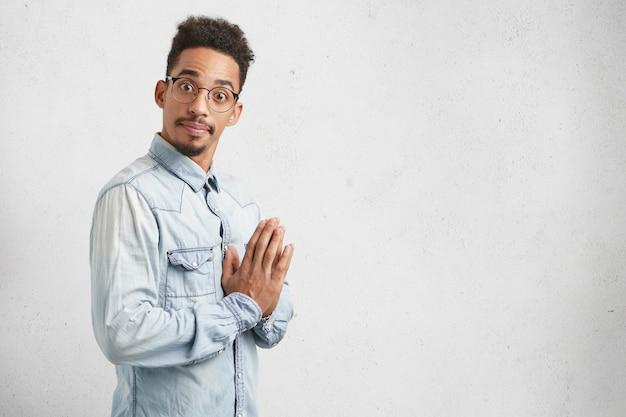 Grappige mannelijke student wil zich niet voorbereiden op examens, hoopt op geluk