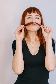Grappige meester van manicure houdt een haarlok door haar handen op haar gezicht in de studio