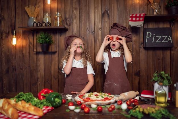 Grappige meisjes die pizza koken en met tomaten en sla voor de gek houden