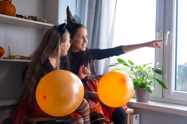 Grappige meisjes in halloween-heksenkostuums met ballonnen kijken uit het raam