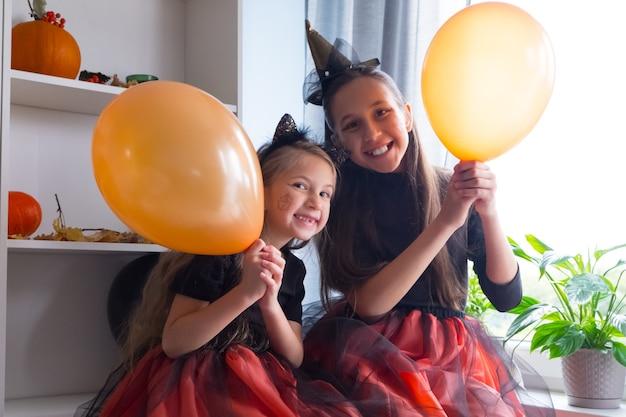 Grappige meisjes in halloween-heksenkostuums met ballonnen vieren de vakantie met vreugde