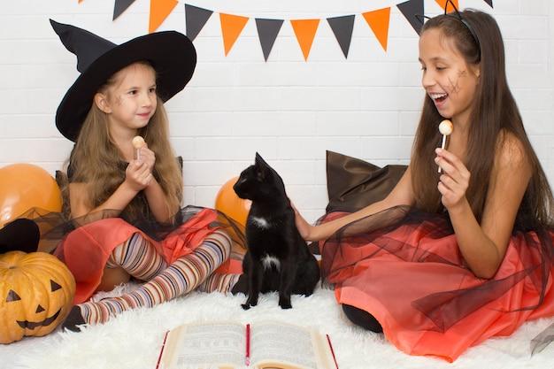 Grappige meisjes in heksenkostuum voor halloween met pompoen jack oranje ballonnen zitten zwarte kat te strelen