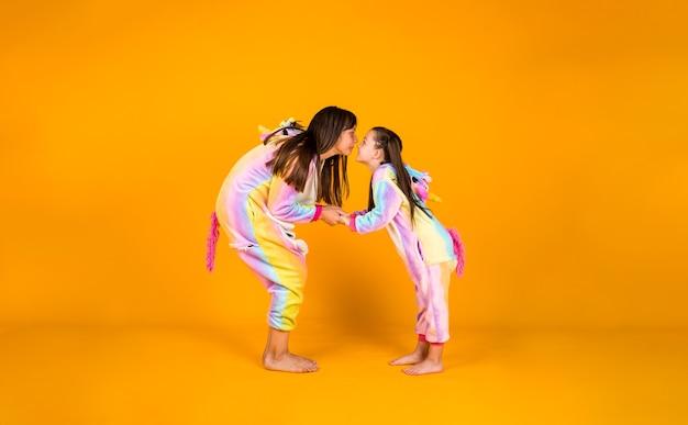 Grappige meisjes in pluche kostuums knuffelen op een gele achtergrond met een plek voor tekst