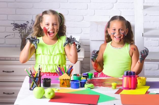 Grappige meisjes kinderen schilders schilderen met gouache verf
