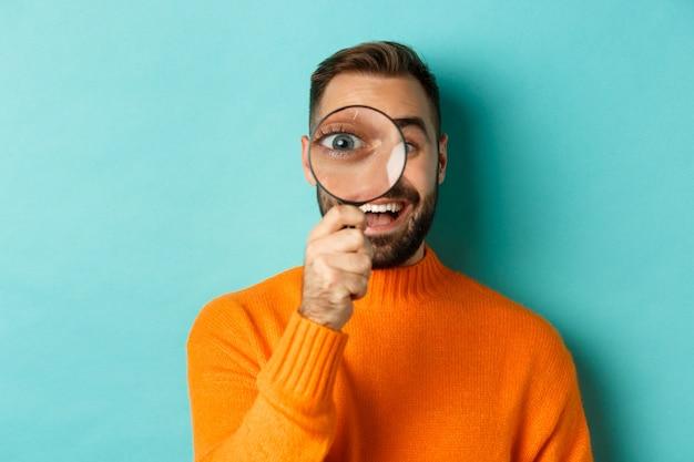 Grappige mens die door vergrootglas kijkt, iets zoekt of onderzoekt, staand in oranje sweater