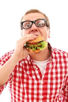 Grappige mens die in glazen hamburger eet die op een wit wordt geïsoleerd
