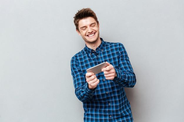 Grappige mens die lacht tijdens het spelen met smartphone