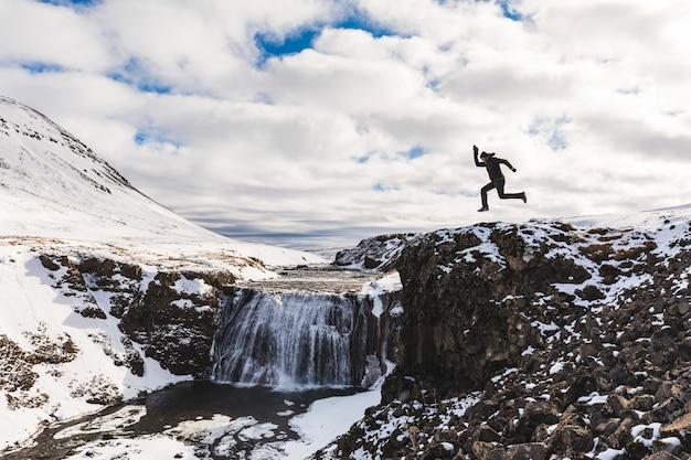 Grappige mens die naast waterval in ijsland springt